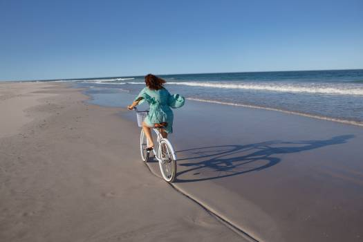 Woman riding bicycle on beach in the sunshine Free Photo