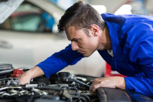 Mechanic servicing a car engine Free Photo