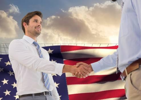Businessman shaking hands against american flag background #411126