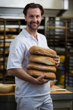 Smiling baker carrying stack of baked breads #411145