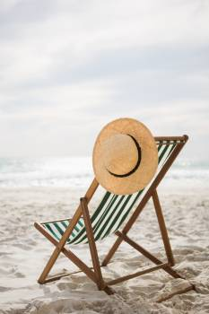 Straw hat kept on empty beach chair #411170