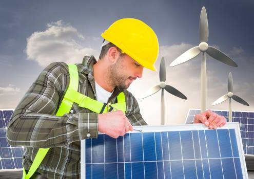 Worker fixing solar panel with wind turbine in background #411212