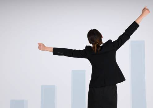 Businesswoman with arms stretched widely against charts incrementing Free Photo