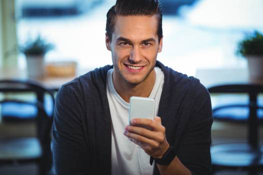 Smiling man using mobile phone in cafe Free Photo