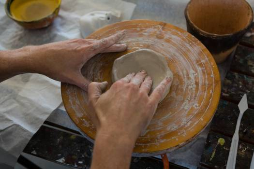 Cropped hand of craftsperson making clay product on pottery wheel #411240