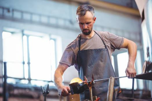 Glassblower forming and shaping a molten glass #411272