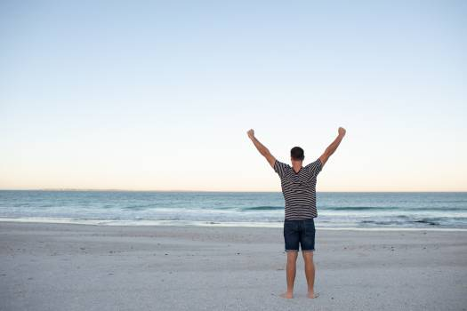 Man standing with arms outstretched on the beach  #411297