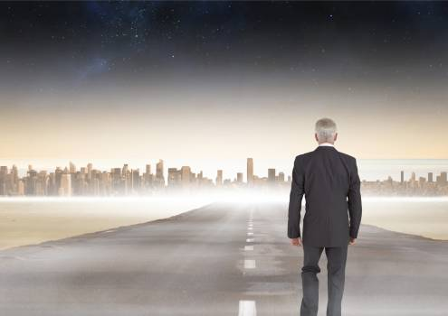 Businessman walking on road to city Free Photo