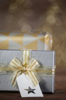 Close-up of wrapped gift box with tag on wooden table Free Photo