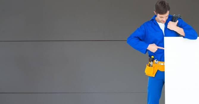 Handyman pointing at blank bill board against wall #411388