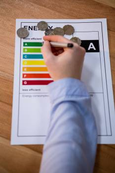 Woman writing on energy efficiency rating chart #411428