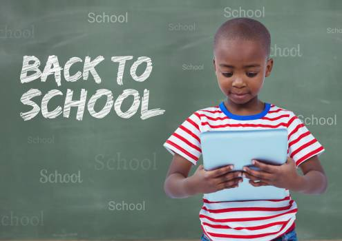 Boy holding digital tablet with back to school text in background #411435