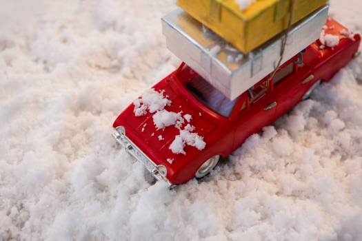 Toy car carrying christmas present on fake snow #411455