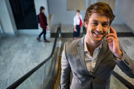 Businessman on escalator talking on mobile phone #411466