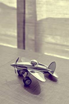 Sepia Photography of Stainless Steel Biplane on Brown Wooden Table Near Window during Daytime Free Photo