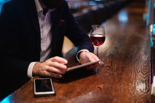 Businessman using digital tablet with wine glass and mobile phone on counter #411502