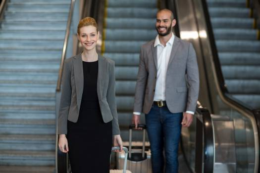 Smiling businesspeople with luggage moving down on escalator #411505