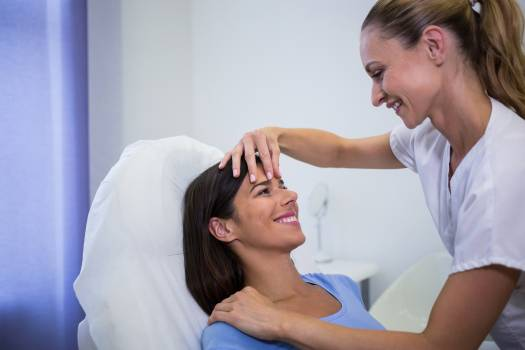 Doctor examining female patients face at clinic Free Photo