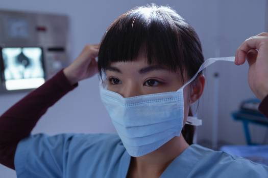 Female surgeon wearing surgical mask in operation room at hospital #411535