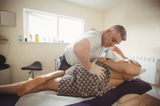 Physiotherapist examining back of a patient Free Photo
