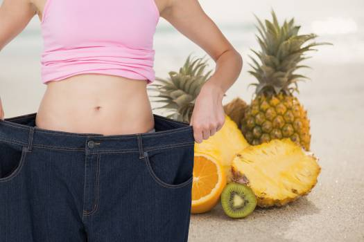 Midsection of woman in loose jeans by pineapples representing weight loss #411548