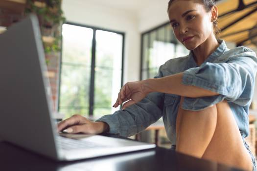 Woman using laptop on worktop in kitchen at comfortable home Free Photo