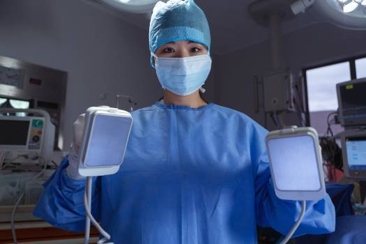 Female surgeon standing with defibrillator in operation room at the hospital #411561