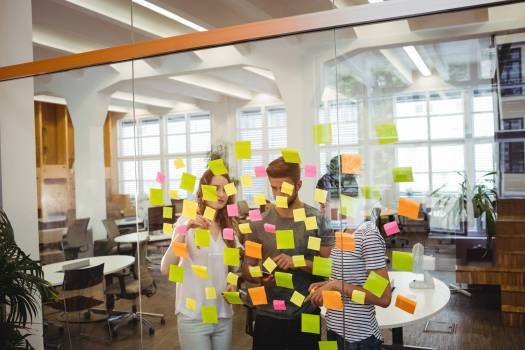 Business executives standing near glass with sticky notes and discussing over digital tablet #411565