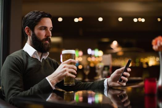 Man looking at mobile phone while having glass of beer #411593