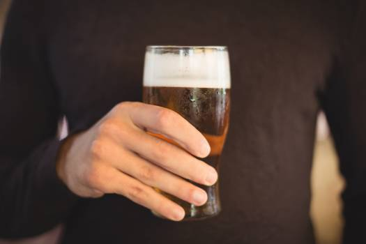 Mid section of man holding glass of beer #411595