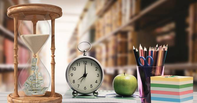 Hour glass, alarm clock, apple and pen holder against library in background #411601