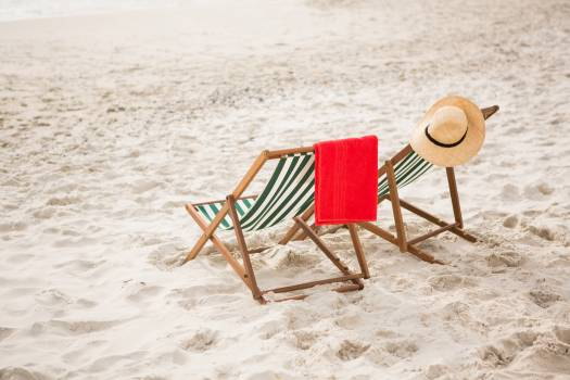 Straw hat and towel kept on beach chairs #411605