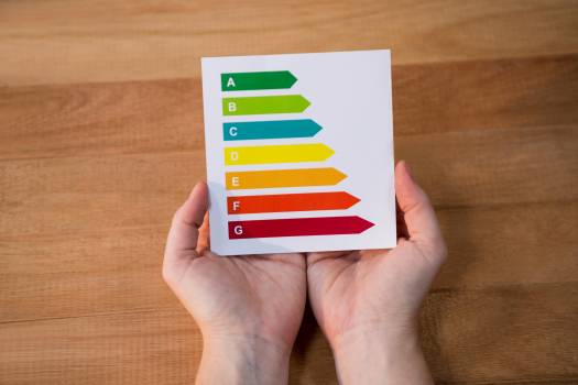 Woman holding energy efficiency rating chart on a wooden table #411610