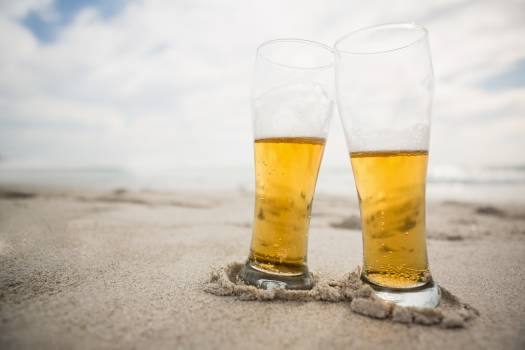 Two beer glasses kept on sand #411718