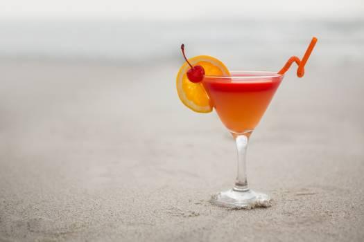 Glass of cocktail drink kept on sand #411719