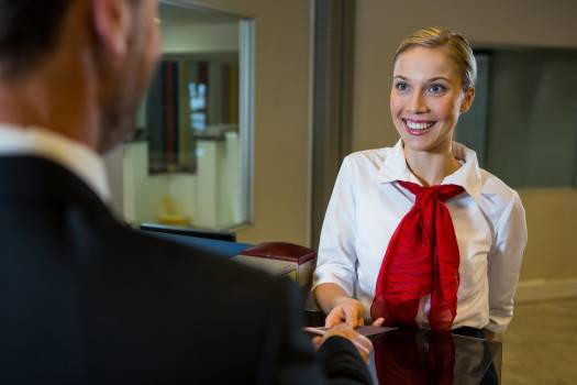 Female staff giving boarding pass to the businessman #411750