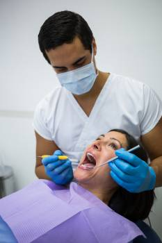 Dentist examining female patient teeth #411781
