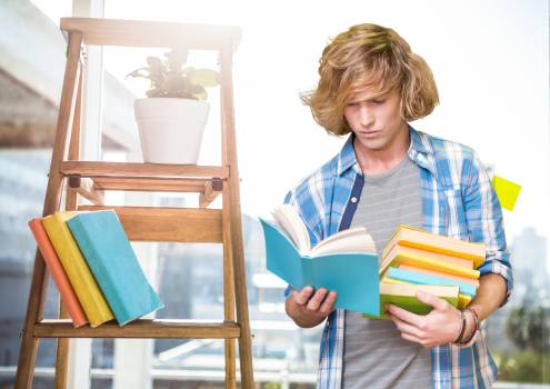 Boy reading books against school in background #411783