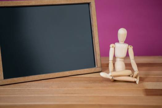 Figurine sitting near a chalkboard #411790