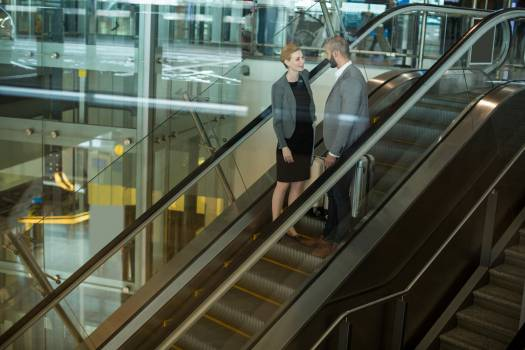 Businesspeople interacting with each other while going up on escalator #411792