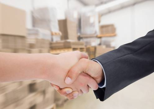 Business executives shaking hands against warehouse in background #411843
