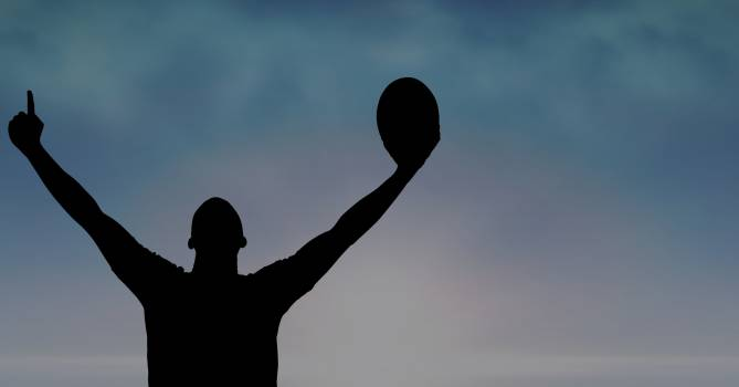 Silhouette man with arms raised holding rugby ball Free Photo