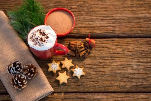 Pine cone, coffee cup, sweet food, cinnamon and christmas fir with napkin Free Photo