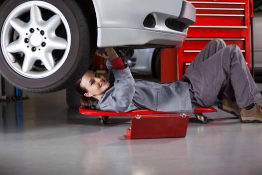 Portrait of female mechanic repairing a car #411953