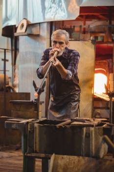Glassblower shaping a glass on the blowpipe #411966