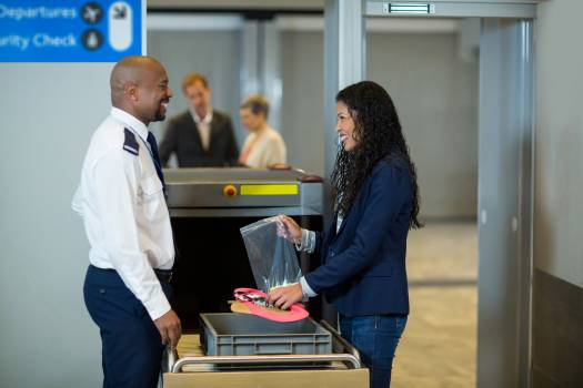 Smiling commuter interacting with airport security officer while collecting accessories from crate Free Photo