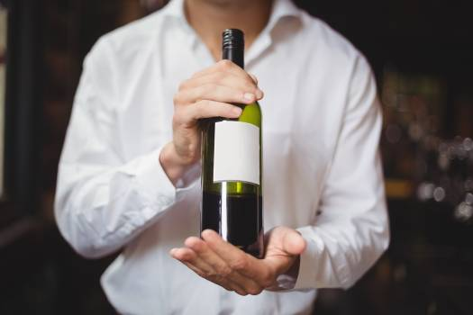 Mid section of bar tender holding a bottle of wine #412034