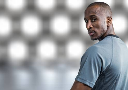 Confident athlete standing against white grey background #412035