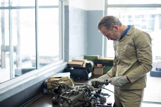 Mechanic checking a car parts Free Photo