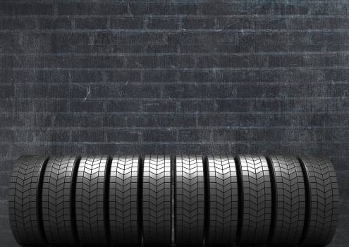 Stack of tyres against black brick background #412042